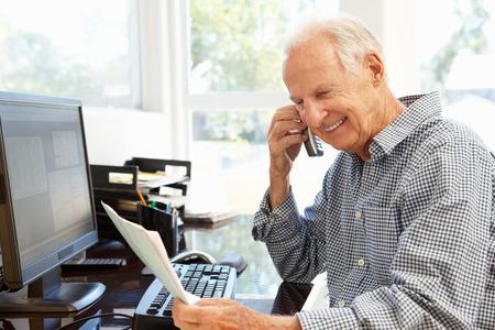 hablando por celular: Hombre mayor que trabaja en casa