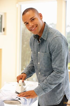 Mixed race man ironing