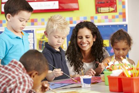 小学校低学年小学生の先生と美術の授業でのグループ