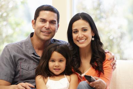 personas viendo television: Familia hispana viendo la televisión