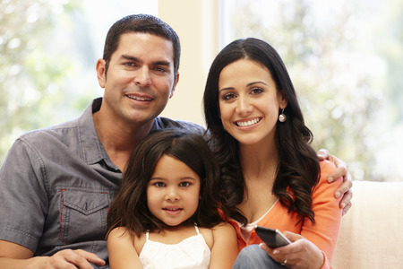 happy family at home: Hispanic family watching television