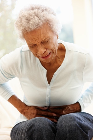 doubled: Senior woman with stomach ache