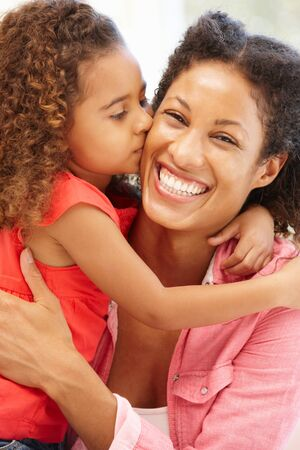 mixed race girl: Mixed race girl kissing mother Stock Photo