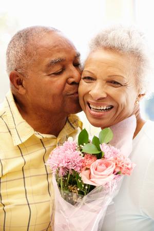 Esposas: Hombre mayor que da las flores a la esposa