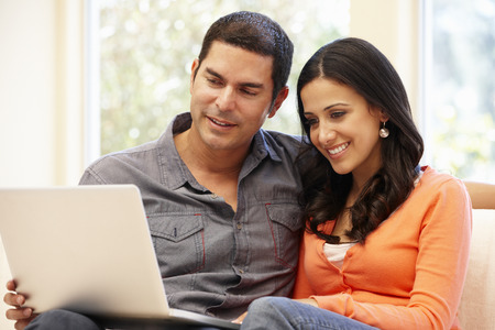 Hispanic couple at home with laptop