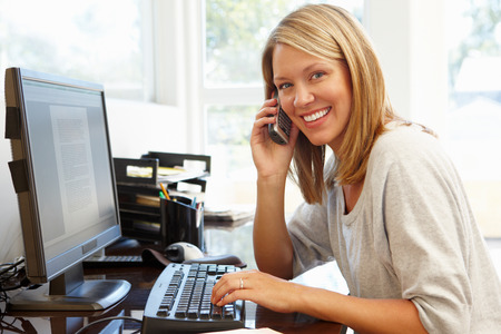 phone conversations: Woman working in home office Stock Photo
