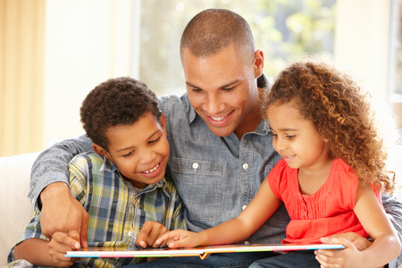 child: Father reading to children Stock Photo