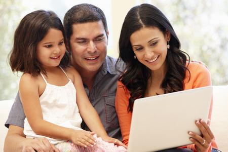 padres e hijos felices: Familia hispánica con la computadora portátil en casa Foto de archivo