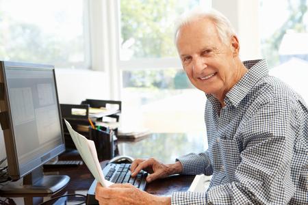 Senior man werkt op de computer thuis Stockfoto