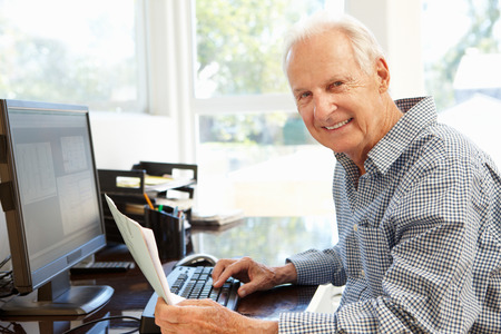 male senior adult: Senior man working on computer at home Stock Photo