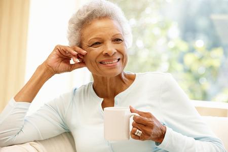 mujer tomando cafe: Mujer mayor del afroamericano en el hogar Foto de archivo