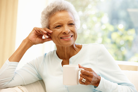 woman on couch: Senior African American woman at home Stock Photo