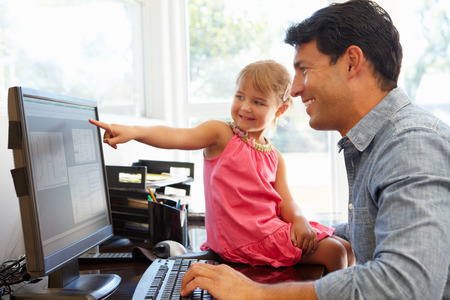 Father working in home office with daughter Zdjęcie Seryjne