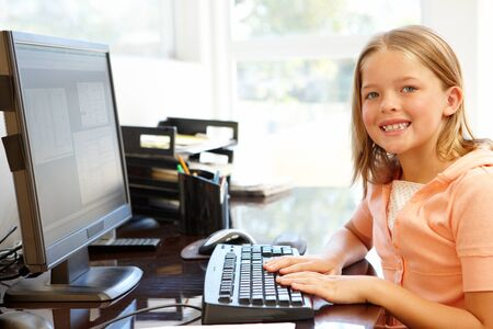 7 year old girl: Young girl using computer at home