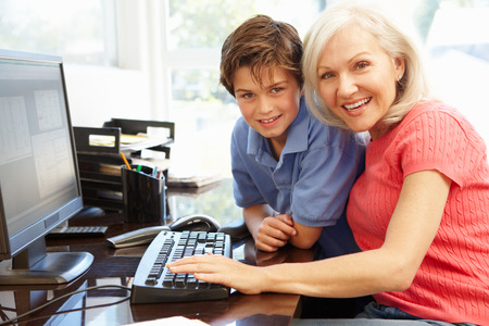 man working computer: Mid age woman and grandson using computer
