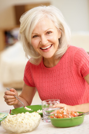 mid age: Mid age woman eating meal Stock Photo