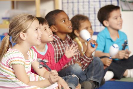 niños sentados: Grupo de primaria Alumnos en la clase de música con los instrumentos Foto de archivo