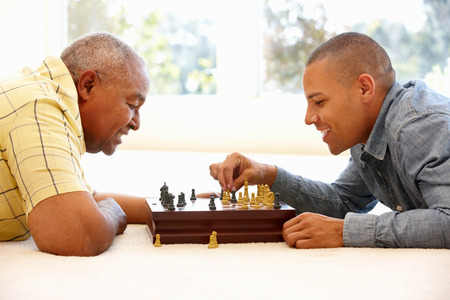 Senior man playing chess with son Stockfoto