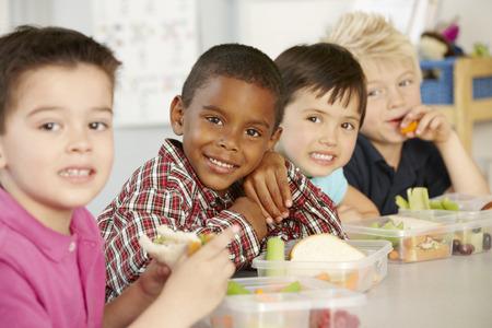 Группа элементарных возраст школьников едят здоровую упакованный ланч класса Фото со стока