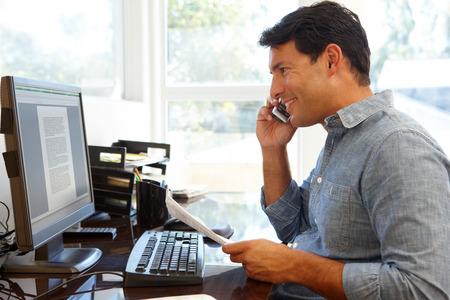 personas trabajando en oficina: Hombre que trabaja en la oficina en casa