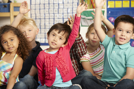 Group Of Elementary Age Schoolchildren Answering Question In Class