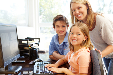 7 year old girl: Mother and children using computer at home