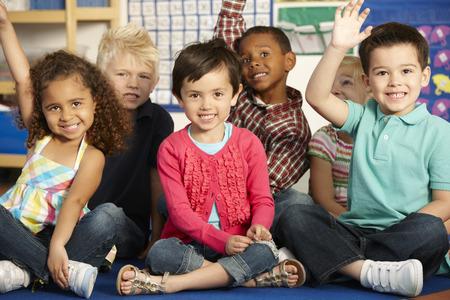 Groep Lagere schoolleeftijd Schoolkinderen beantwoorden Vraag In Klasse