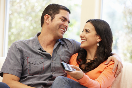 television remote: Hispanic couple watching television