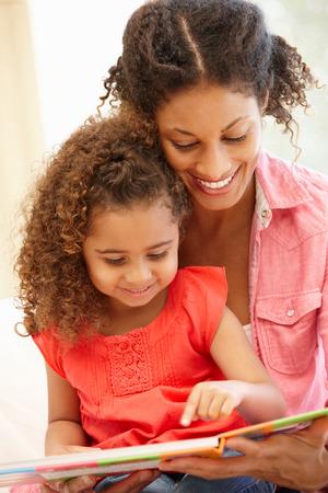 niños sentados: Mujer de raza mixta y la lectura hija