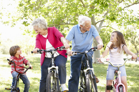 active woman: Senior couple with grandchildren on bikes