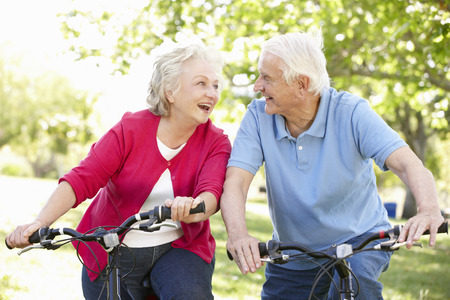 an elderly person: Senior couple riding bikes Stock Photo