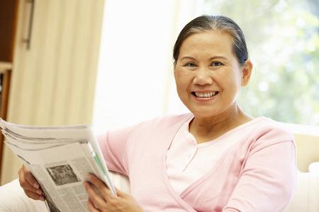 gente adulta: Periódico lectura de la mujer asiática mayor Foto de archivo