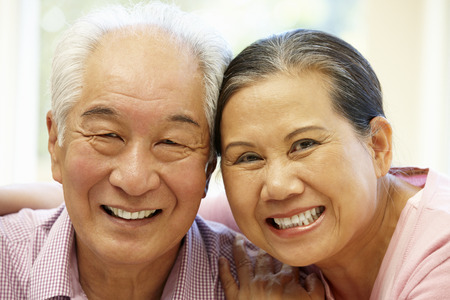 woman on couch: Senior Asian couple at home Stock Photo