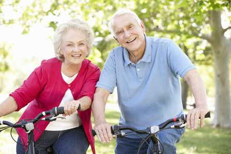 older men: Senior couple riding bikes Stock Photo