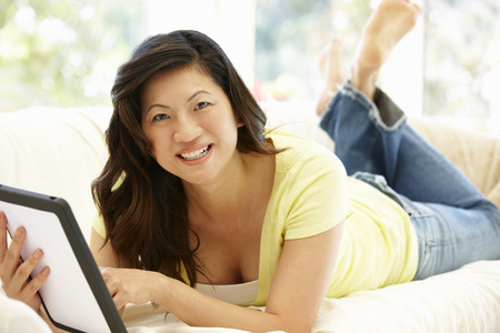 Asian woman using tablet at home Stock Photo