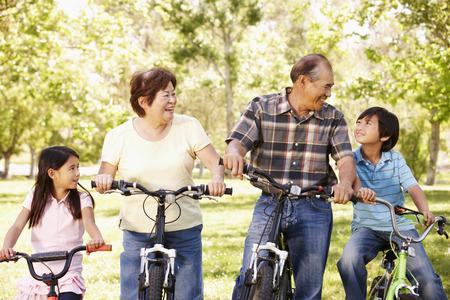 abuelos: Los abuelos de Asia y nietos que montan las bicis en el parque Foto de archivo