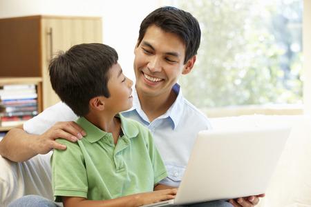 supervisión: Padre e hijo usando la computadora portátil