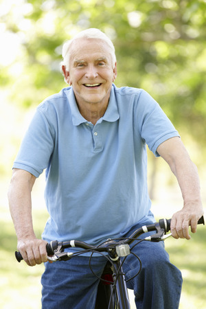 Senior man riding bike Stock Photo