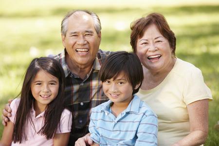 grandad: Portrait Asian grandparents and grandchildren in park