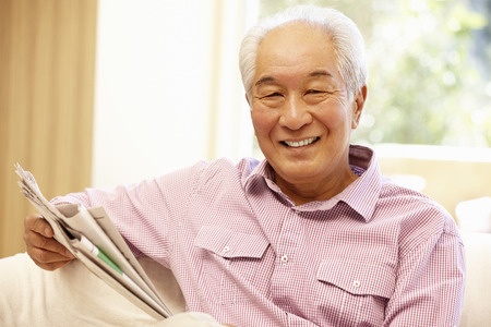 Senior Asian man reading newspaper Stock Photo