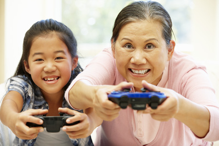 video game: Senior Asian woman and girl playing video game