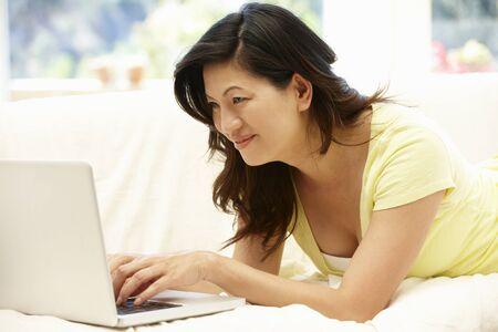 browsing: Asian woman using laptop at home