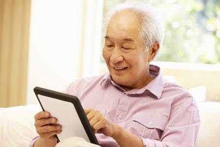 tercera edad: Hombre asiático mayor que usa la tableta Foto de archivo