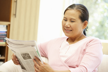 greying: Senior Asian woman reading newspaper