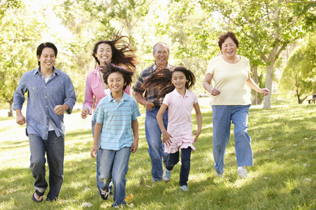 thirties portrait: Multi-generation Asian family running in park