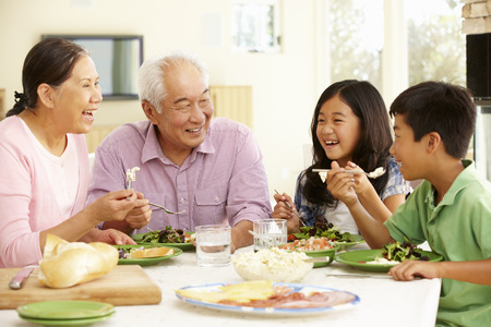 a year older: Asian family sharing meal at home Stock Photo