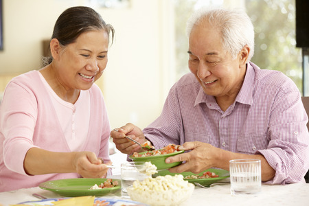 pareja comiendo: Mayor asi�tico comida compartir pareja en el hogar Foto de archivo
