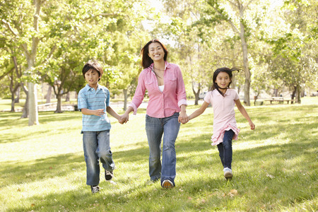 7 year old boys: Asian mother and children running hand in hand in park Stock Photo