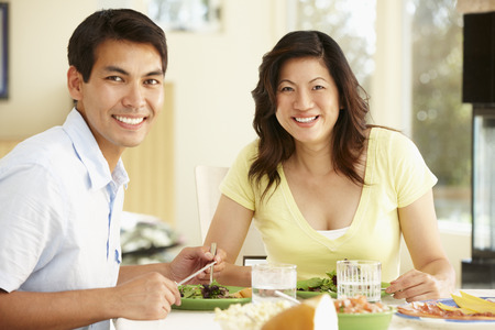 happily: Asian couple sharing meal at home Stock Photo