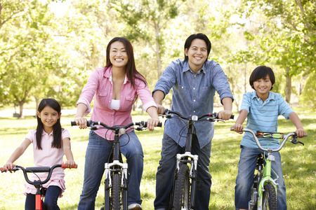 asian trees: Asian family riding bikes in park